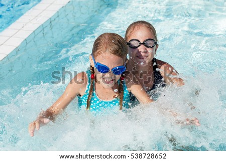 Two happy children playing on the swimming pool in aqua park at the day time.  People having fun outdoors. Concept of friendly family and  summer vacation.