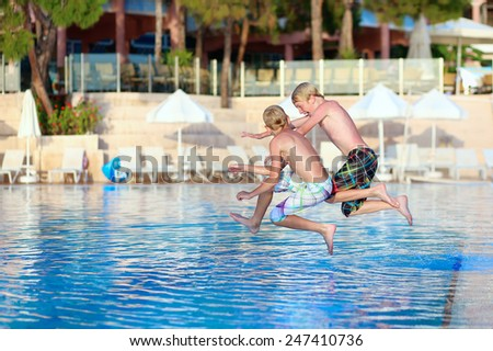 Two happy children, twin brothers are jumping into swimming pool at the resort at sunset