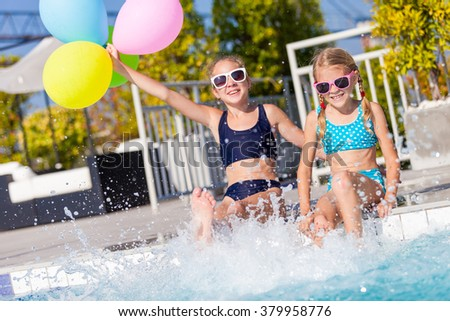 Two happy children with balloons playing on the swimming pool in aqua park at the day time. Concept of friendly family. - stock photo