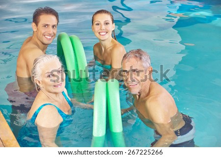 Two happy couples in aqua fitness class in a swimming pool with swim noodles - stock photo