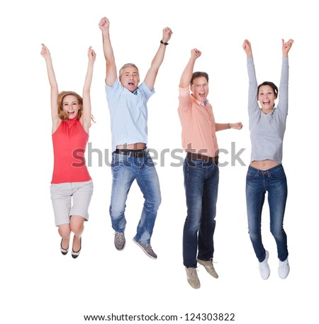 Two happy couples in casual clothing jumping in the air rejoicing with their arms raised isolated on white - stock photo