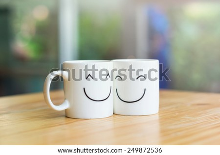 Two happy cups on the wood table, about love concept - stock photo