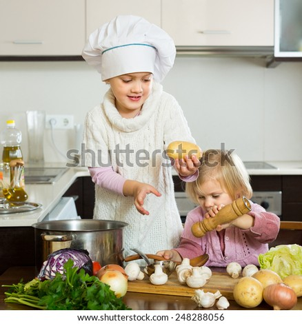 Two happy cute little sisters with pot smiling at home kitchen