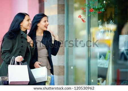 two happy elegant women looking in shop window - stock photo