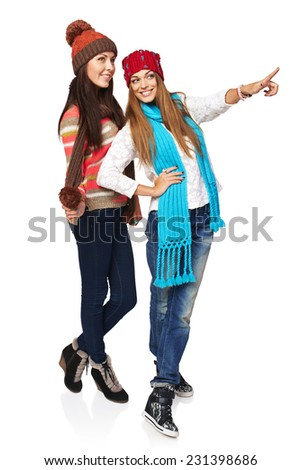 Two happy female friends wearing winter clothing standing in full length thinking looking and pointing away at blank copy space, white background - stock photo