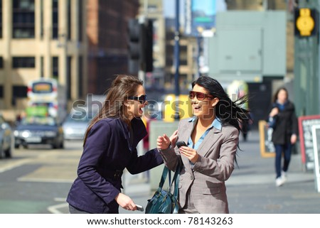 two happy females laugh and have good time together, elegant business look, wears coat and suit with shirt, background is blurred - stock photo