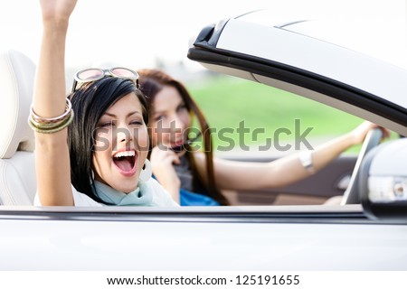 Two happy friends in the white car driving everywhere and looking for freedom and fun