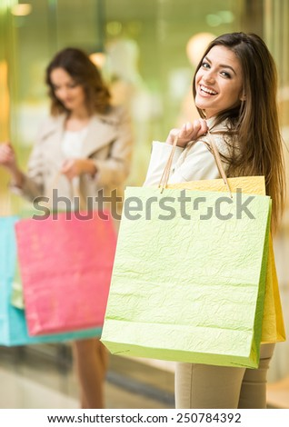 Two happy friends is shopping in mall. - stock photo