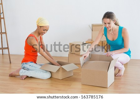Two happy friends moving together in a new house and unwrapping boxes - stock photo