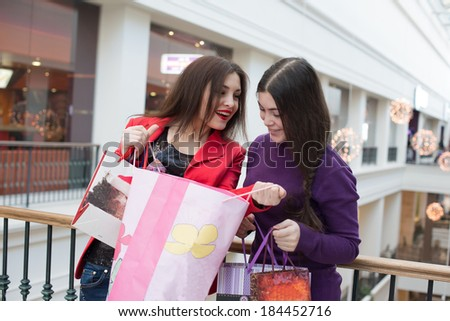 two happy friends shopping in mall, look at their purchase