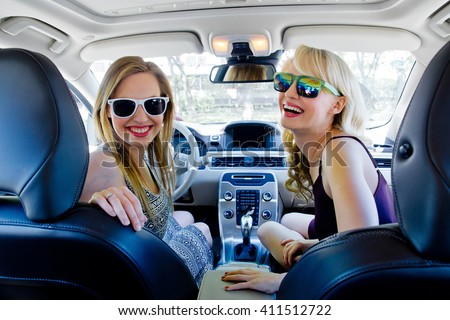 two happy girl friends in the car having fun