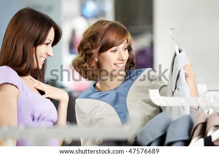 Two happy girlfriends consider clothes in shop - stock photo