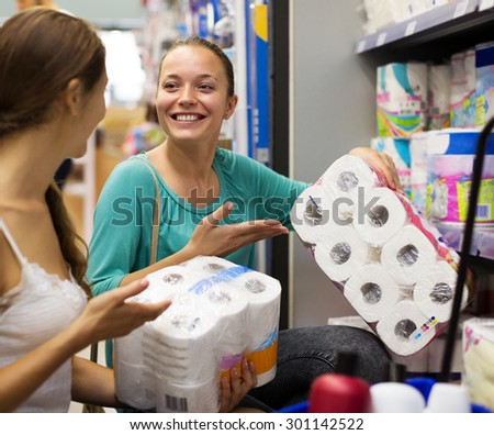 Two happy girls choose toilet paper in the shop - stock photo