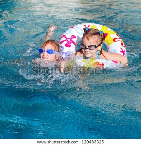 two happy  girls  in the pool  with rubber ring