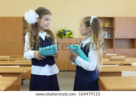 Two happy girls in uniform stand in classroom with exercise books and talk at school. - stock photo