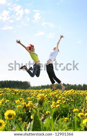 two happy girls jumping outdoors - stock photo
