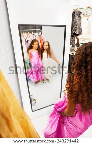 Two happy girls look into the mirror - stock photo