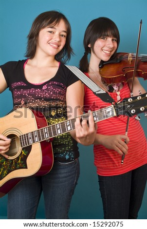 Two happy girls, one with a guitar and one with a violin or viola. - stock photo