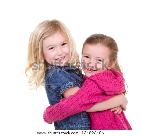 Two happy girls or children hugging each other on an isolated white background - stock photo
