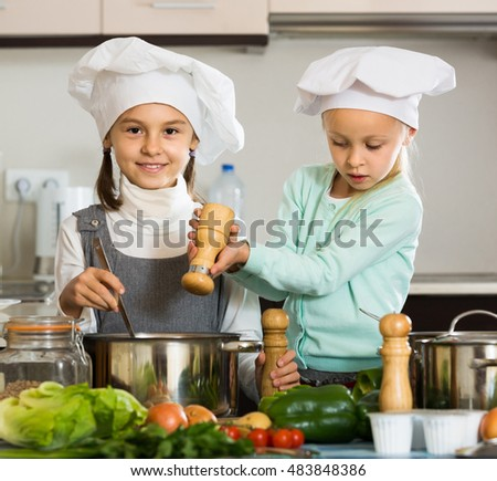 Two happy girls preparing vegetables and smiling indoors
