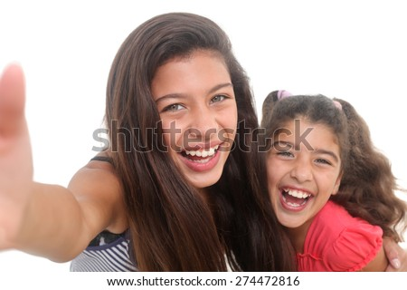 two happy girls taking a selfie on a white background - stock photo