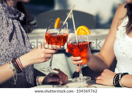 two happy girls while they drink a cocktail - stock photo