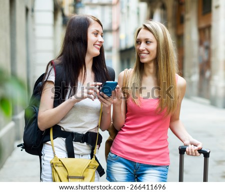 Two happy girls with baggage using the navigator at smartphone