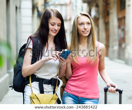 Two happy girls with bags using the navigator at smartphone