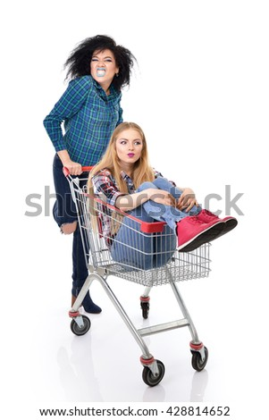 Two happy hipster girls have fun in supermarket's trolley over white background - stock photo