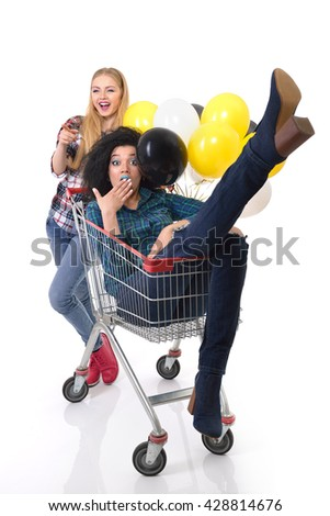 Two happy hipster girls have fun in supermarket's trolley with balloons over white background - stock photo