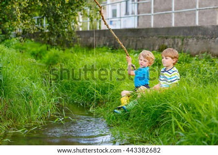 Two happy kid boys fishing on a river with selfmade fishing rod  on sunny summer day. Happy children having fun. Active leisure for children outdoors. - stock photo