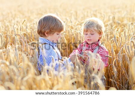 Two happy kid boys with blond hairs in yellow wheat field on warm summer day. Funny Children in traditional German bavarian clothes, leather shorts and check shirt - stock photo