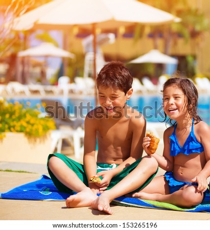 Two happy kids eating croissant near pool, having breakfast on the beach, active summer holidays, brother and sister enjoying sunny day, happiness concept - stock photo