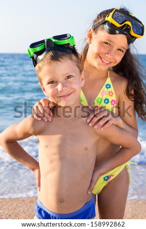 Two happy kids in diving masks standing together on the beach - stock photo