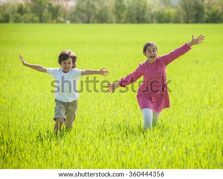 Two happy kids in green wheat - stock photo