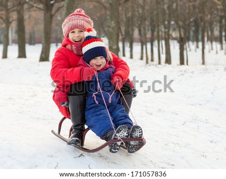 Two happy kids in winter clothes on sled - stock photo