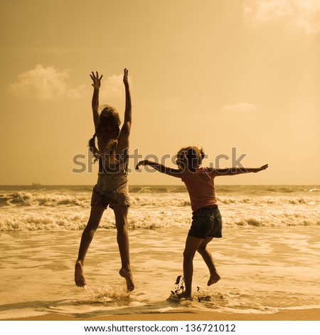 Two happy kids jumping on the beach - stock photo