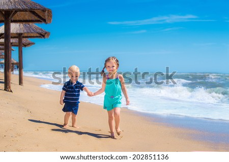 Two happy kids playing in a summer sea, running together along the beach ocean, fun game for boy and girl - stock photo