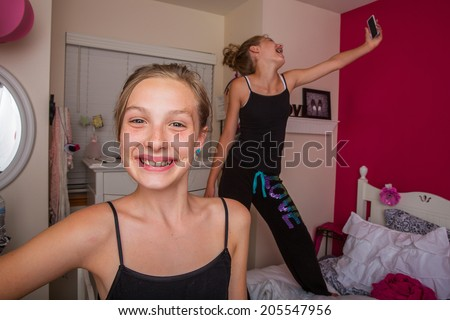 Two happy kids playing in their room and taking selfies with their cellphone - stock photo