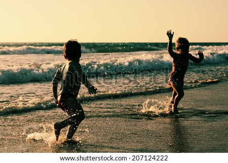 two happy kids playing on the beach at sunset - stock photo