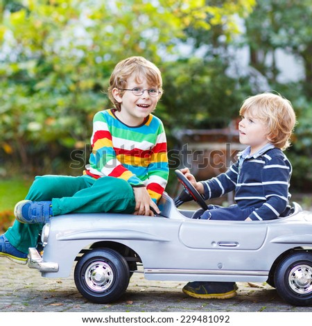 Two happy kids playing with big old toy car in summer garden, outdoors. Siblings and friends on warm day. Square format. - stock photo