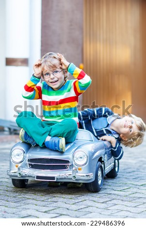 Two happy kids playing with big old toy car in summer garden, outdoors. Siblings and friends on warm day. Selective focus on one boy. - stock photo