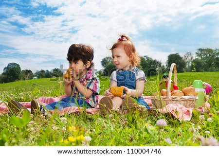 Two happy kids sitting on picnic in the park - stock photo