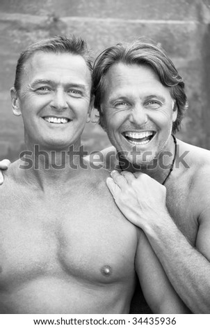Two happy laughing gay men enjoy a cuddle outdoors. - stock photo