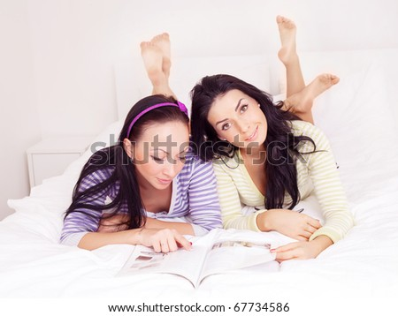 two happy laughing  girls reading a magazine on the bed at home - stock photo