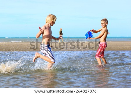 Two happy laughing kids, teenage boys, twin brothers, having fun at the North Sea playing together on the beach, running and splashing water from bucket - stock photo