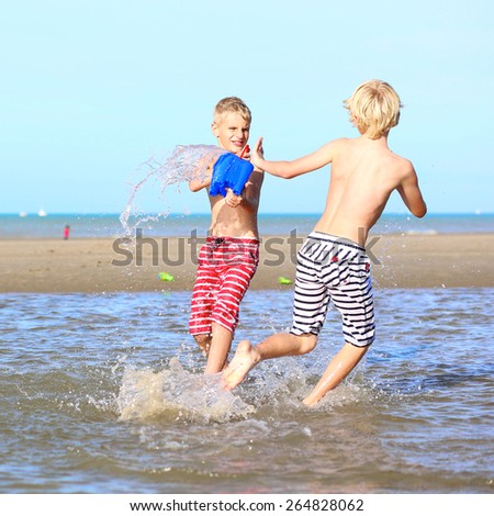 Two happy laughing kids, teenage boys, twin brothers having fun at the North Sea playing together on the beach, running and splashing water from bucket