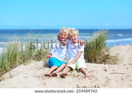 Two happy laughing kids, twin teenager brothers, enjoying summer vacation on sunny day having fun on the beach playing in sandy dunes, North Sea, Belgian coast - stock photo
