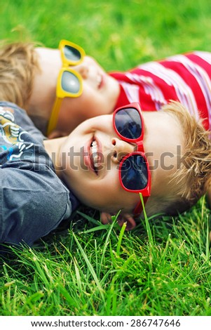 Two happy little boys lying on the grass - stock photo