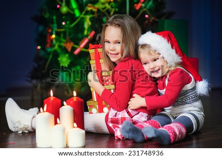 two happy little fashion girls  in Santa Hat with Christmas light and eve and candy - stock photo